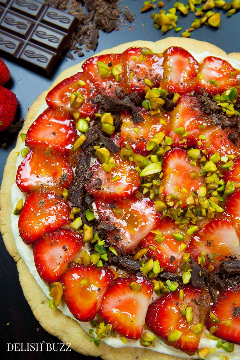 Easy delicious summery gluten free strawberry pizza. Very refreshing and full of subtle flavors. Strawberries on a sugar cookie crust with a layer of light lemon scented creamy frosting with apricot glaze. This will be a show stopper on any dining table. www.delishbuzz.com