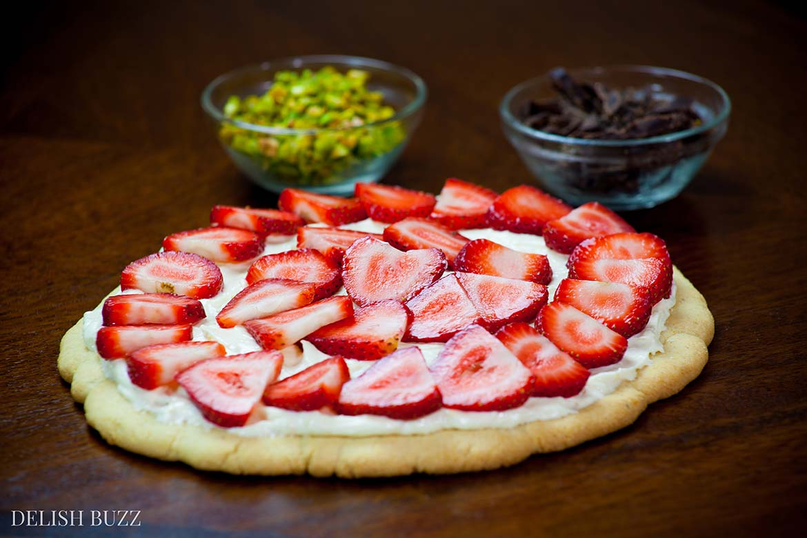 Strawberry pizza prep. Easy delicious summery gluten free strawberry pizza. Very refreshing and full of subtle flavors. Strawberries on a sugar cookie crust with a layer of light lemon scented creamy frosting with apricot glaze. This will be a show stopper on any dining table. www.delishbuzz.com