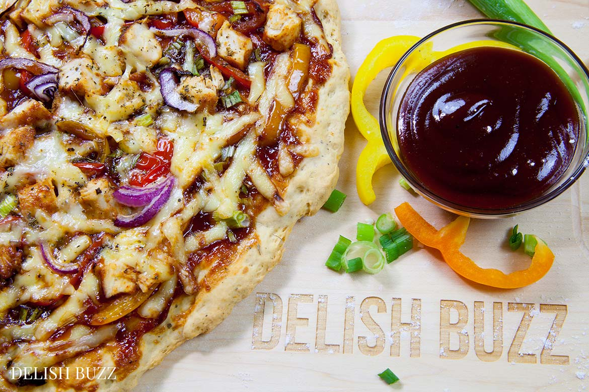 This pizza is full of flavor! Easy Barbeque Chicken Pizza explodes with flavors in your mouth. Instant no rise homemade crust along with barbeque sauce, sweet peppers and gouda cheese makes this pizza irresistible. www.delishbuzz.com