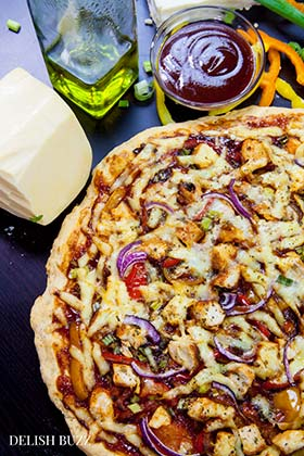 Smoked Gouda and smoked paprika do wonders here! Easy Barbecue Chicken Pizza explodes with flavors in your mouth. Instant no rise homemade crust along with barbecue sauce, sweet peppers and gouda cheese makes this pizza irresistible. www.delishbuzz.com