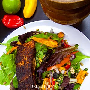 Close up of our finished salad! Vibrant and fragarant! A very satisfying aroma rich creamy blackened salmon salad with a creamy homemade gingery dressing! Crunchy, creamy, salty, sweet salad with juicy salmon. www.delishbuzz.com